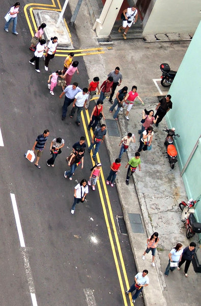 angle on pedestrians: looking down on group of tourist pedestrians sauntering along road