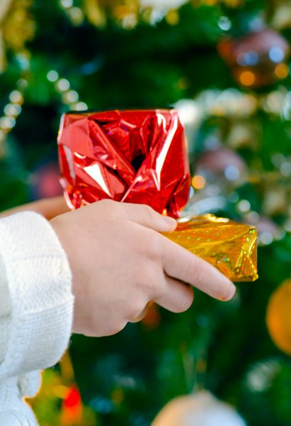 Christmas presents: Child presenting Christmas gifts in front of a tree