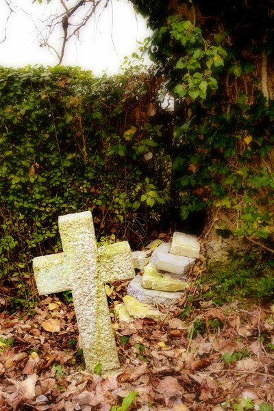 Forgotten: Old cross in a corner of a graveyard