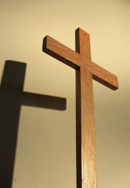 Cross with shadow: Close-up of small wooden cross, and its shadow on a wall