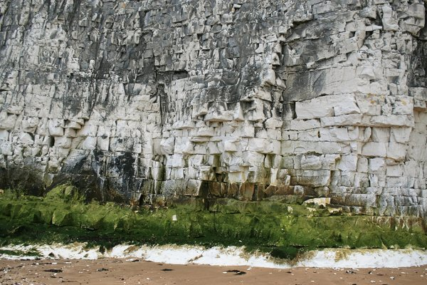 Chalk cliff face: Chalk cliff at low tide on a beach in Kent, England.