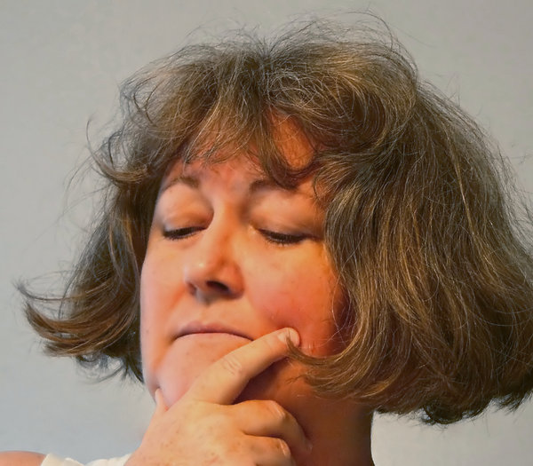 Depression: A woman with hand to her face, looking downward, with a depressed and worried expression. Similar pics here: