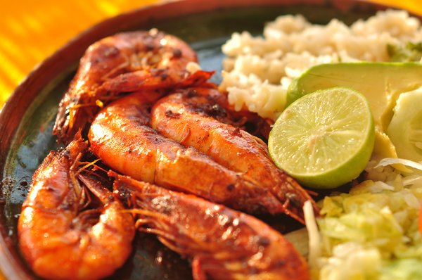 Plate of shrimp mexican food: Plate of mexican food: shrimp, rice, avocado, lemon and lettuce on a hand-made plate.