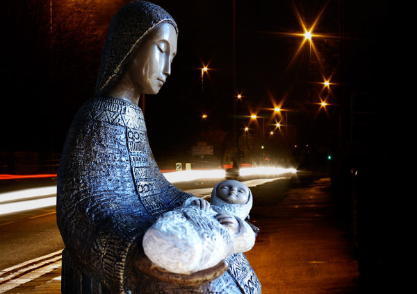 Nativity in the city: Nativity - mother and child - with star light glowing from street lights