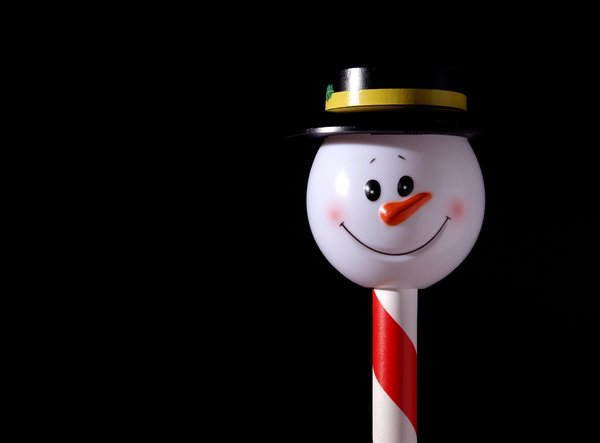 Snowman on a stick: Happy snowman on a candy stick isolated with black background