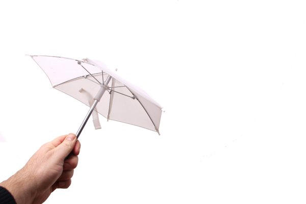 Holding small white umbrella: Hand holdning small white umbrealla (used for flash) isolated from the white background