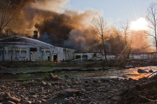 Inferno: Figher Fighters battle a Factory warehouse fire at sunset across a stream. Taken in Cornwall, New York. Contact me for Hi-Res.