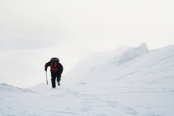 Mountaineering in Scotland: A man climbing a snowy mountain in Scotland