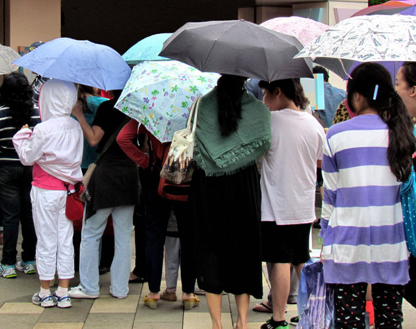 queuing in the rain: people queuing up while it's raining