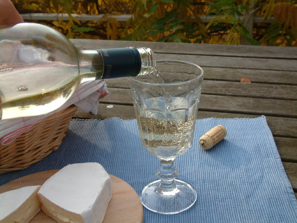 Wine and cheese: Serving cold white wine and cheese on a balcony