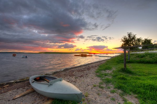 Hunting boat - HDR: Small boat for hunting in the sunset and boats being at anchor. The images is HDR