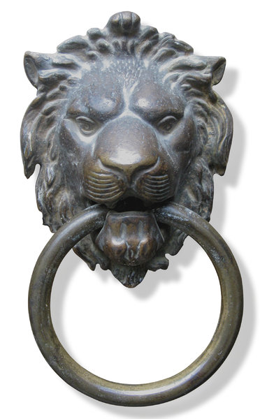 lion head knocker: bronze knocker in shape of a lion head with a ring in its mouth