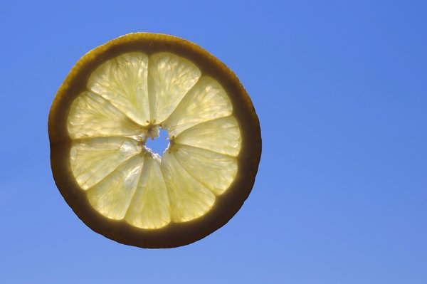 Flying lemon: Slice of lemon flying with a clear blue sky as a background