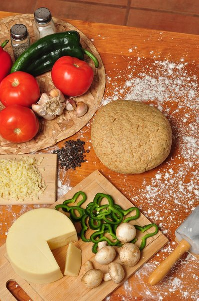 Pizza dough and ingredients: Pizza ingredients and whole-wheat dough on a wooden table sprinkled with flour