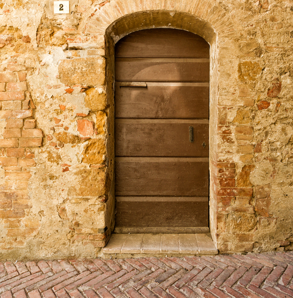 Door in ancient House: Old Door to an ancient House - Pienza, Tuscany, Italy. Nice antique Paving.
