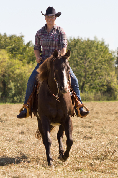 Equitation - Western Riding: Equitation - Western Riding. Young Woman riding a Quarter Horse outdoors in a Field.