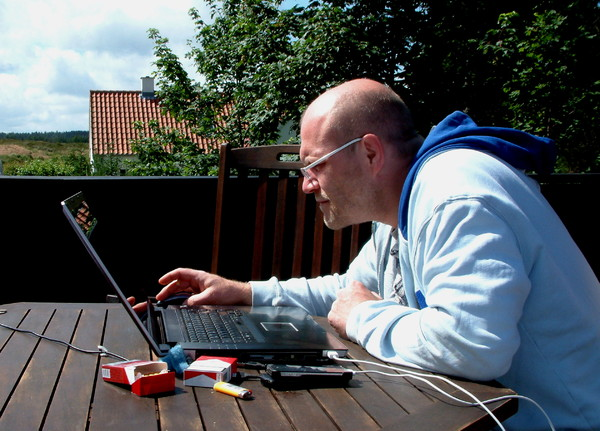 Man at work: Working with a laptop outside on a terrace