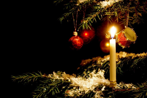 Christmas tree with candle: Christmas tree with candle and ornaments. Black background.
