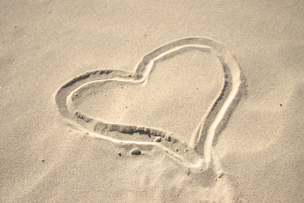 Sand heart 2: A sand heart drawn in the sand on the beach