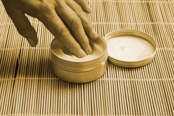 Skin care: Taking skin cream from a pot