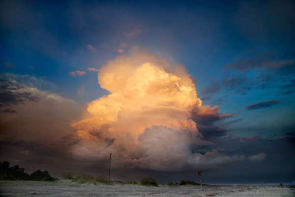 Storm cloud on fire: Cumulus cloud at the edge of an late evening storm above the beach of an island. The light was failing