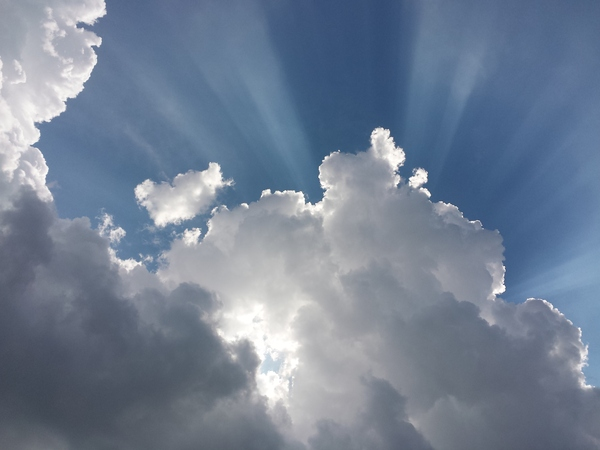Sun & Clouds: Sunrays illuminate the blue sky behind some impressive clouds